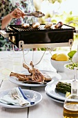 A table laid outside with grilled lamb chops