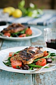 Beef steak with anchovies, green beans, tomatoes and olives