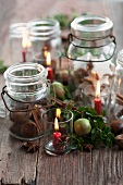 Cinnamon stars, chestnuts and cinnamon sticks in jars between candles