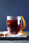 A glass of mulled wine with orange peel