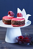 Mini cakes on a cake stand with sugared raspberries