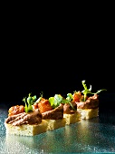 Mini canapes topped with goose liver mousses and pear chutney