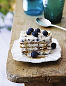 A layered dessert with wafers, stracciatella ice cream and blueberries