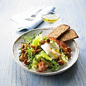 Mixed leaf salad with chanterelle mushrooms, soft-boiled egg and bacon