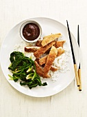 Breaded and Baked Chicken Sliced Over Rice with Dipping Sauce and Wilted Greens