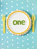 "The word ""one"" spelled out with peas on a plate"