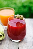 A glass of carrot and orange juice and a glass of beetroot and apple juice