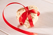 A heart-shaped biscuit tied with a red ribbon