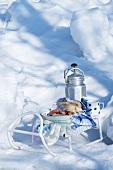 Sausages, bread and a Thermos flask on a sledge in the snow