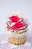 A cupcake decorated with red lips and sugar hearts for Valentine's Day