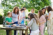 Adults and children standing around the buffet at a garden party