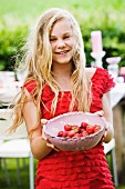 A blonde girl with a bowl of freshly picked strawberries