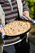 A woman holding an apple cake topped with slivered almonds (Scandinavia)