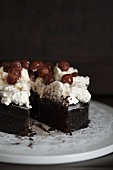 Chocolate cake topped with cream cheese and cherries