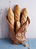 Baguettes in a torn paper bag