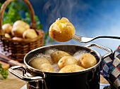 New potatoes in a pot of boiling water and on a fork