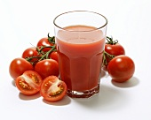 A glass of tomato juice surrounded by tomatoes