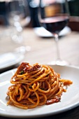 Bucatini All Amatriciana on a White Plate; Glass of Wine