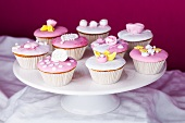 Cupcakes with pink and white glaze and sugar roses on a torte stand