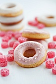 Doughnuts with pink sugar icing and raspberry drops