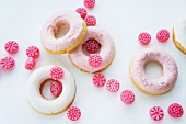 Doughnuts with pink and white sugar icing and raspberry drops