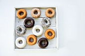 Assorted doughnuts in a wooden box (view from above)