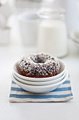 A doughnut with coconut flakes in a stack of bowls