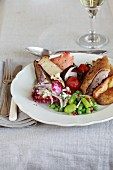 Duck with roast potatoes, mushrooms and cherry tomatoes