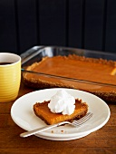 Pumpkin Bar Topped with Whipped Cream; Baking Dish of Pumpkin Bars in Background