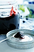 Blueberry jam in jar and on a spoon