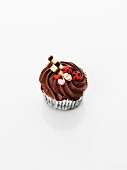 A cupcake decorated with chocolate cream, ladybirds and hearts