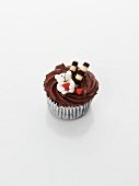 A cupcake decorated with chocolate cream, a teddy bear and hearts