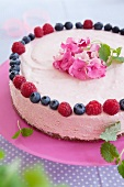 Raspberry mousse layer cake with raspberries, blueberries and flower decoration