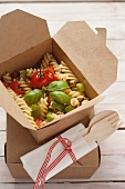 Fusilli with tomatoes, courgette and basil in a takeaway box