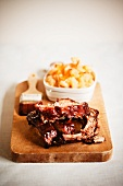 Barbecue Pork Ribs on a Cutting Board with a Bowl of Macaroni and Cheese