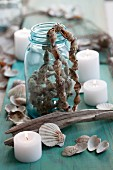 A jar with a string of shells and candles