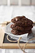 Three chocolate biscuits stacked on grease-proof paper on a blackboard