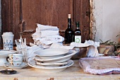 Plates, cups, glasses, tea towels and wine bottles on a rustic wooden table