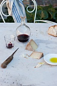 An old cheese knife, red wine, bread, Parmesan and olive oil