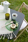 An espresso pot, mug of coffee and a glass plate with a sweet pastry on a garden table