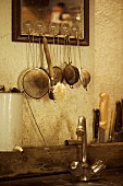 Sieves & washing-up brush hanging above rustic sink