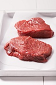 Two steaks on parchment paper on a baking tray
