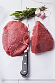 Steaks on baking paper with a knife, herbs and garlic