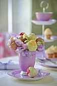Decorated cake pops in a purple cup