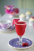 A raspberry daiquiri in a glass with a sugared edge