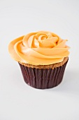 A rose cupcake with orange frosting
