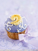 A cupcake decorated with purple icing