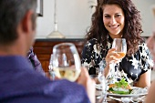 Couple holding glasses of wine at lunch table, smiling at each other
