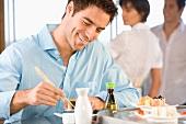 Young man eating sushi, smiling