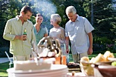 Senior couple talking to adult offspring near garden table at family barbecue, smiling